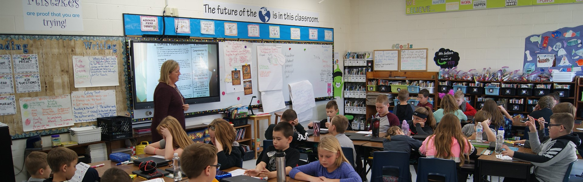 students at desks and teacher in front of room in a 4th grade classroom