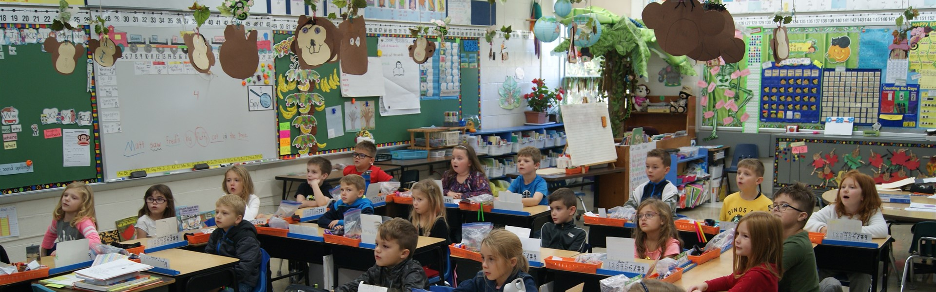 students in 1st grade sitting in desks in a bright, colorful classroom