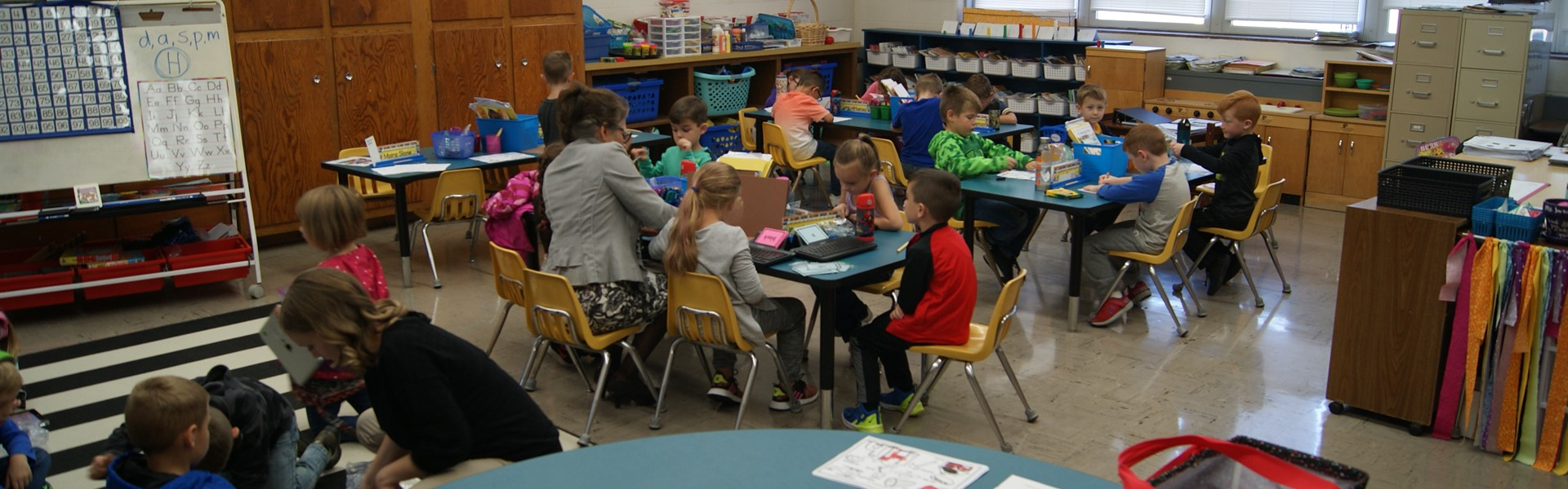 classroom of students and staff working together on reading activities